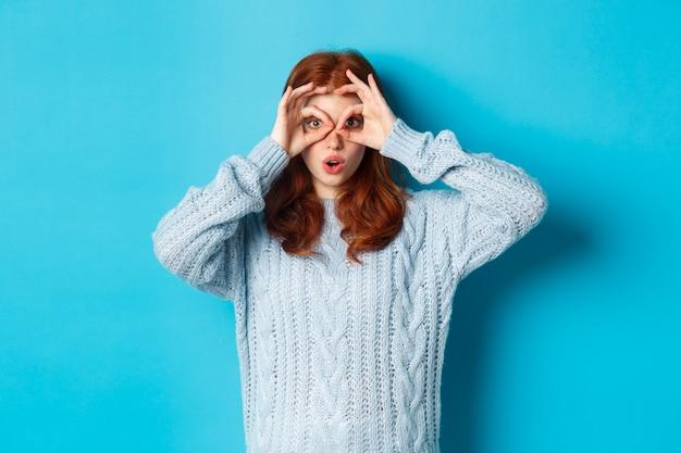 Divertente modello femminile rossa in maglione, fissando la telecamera attraverso gli occhiali delle dita, vedendo qualcosa di interessante, in piedi su sfondo blu