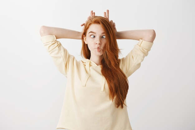 Funny redhead girl grimacing childish