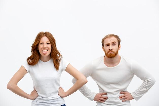 Смешные рыжий мужчина и женщина, показывая гримасы