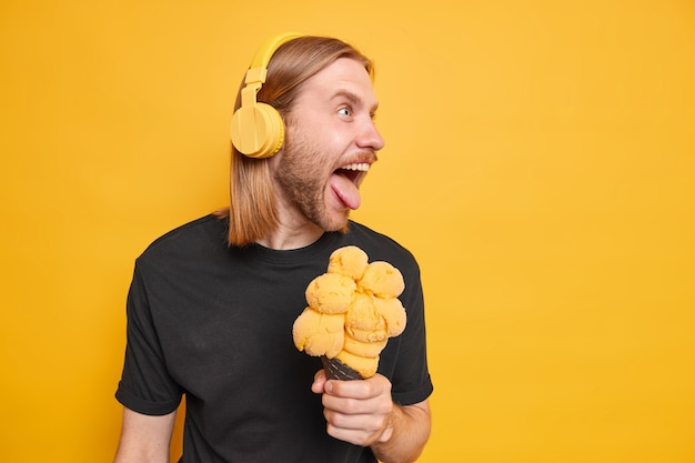 Funny redhead man sticks out tongue keeps mouth wide opened holds tasty ice cream has fun looks away makes funny grimace listens music via headphones dressed in black t shirt isolated on yellow wall