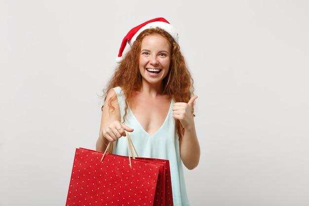 白い背景で隔離のクリスマス帽子の面白い赤毛サンタの女の子。明けましておめでとうございます2020年のお祝いの休日のコンセプト。コピースペースをモックアップします。親指を立てて、ギフトや購入品が入ったパッケージバッグを持ちます。
