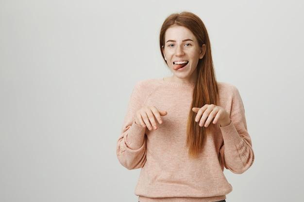 Redhead divertente ragazza sorridente scimmiottando le zampe del cucciolo