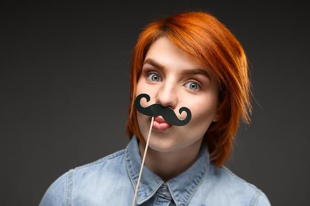 Смешная рыжая женщина носит поддельные усы