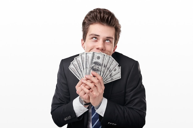 Funny rich young man in formal suit smelling bunch of american dollars and dreaming how to spend money on white background