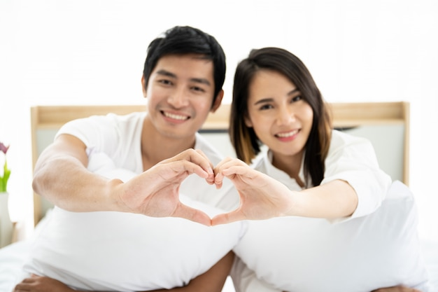 Funny and romantic asian couple' portrait in bedroom with natural light from window, concept of relationship between husband and wife and being a family.