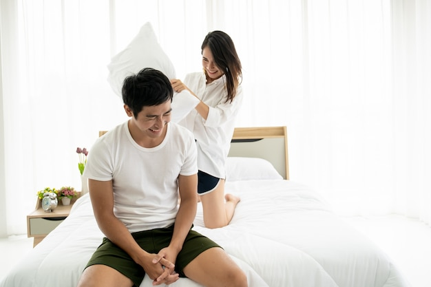 Funny and romantic asian couple' portrait in bedroom with natural light from window,  relationship between husband and wife and being a family.