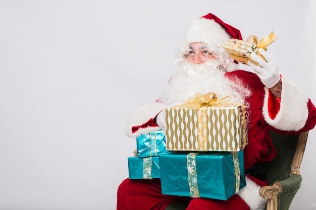 プレゼントと赤い衣装で面白いサンタクロース