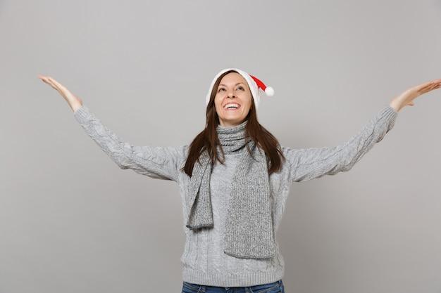 灰色のセーターのスカーフのクリスマス帽子の面白いサンタの女の子が見上げて、灰色の背景に分離されたポインティング手を脇に広げます。明けましておめでとうございます2019お祝いホリデーパーティーのコンセプト。コピースペースをモックアップします。