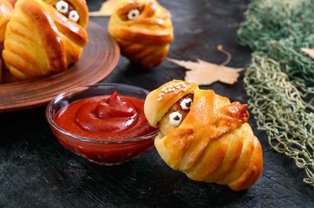 재미있는 소시지와 커틀릿은 눈이 있는 반죽에 미이라, 테이블에는 케첩이 있습니다. 할로윈 음식.