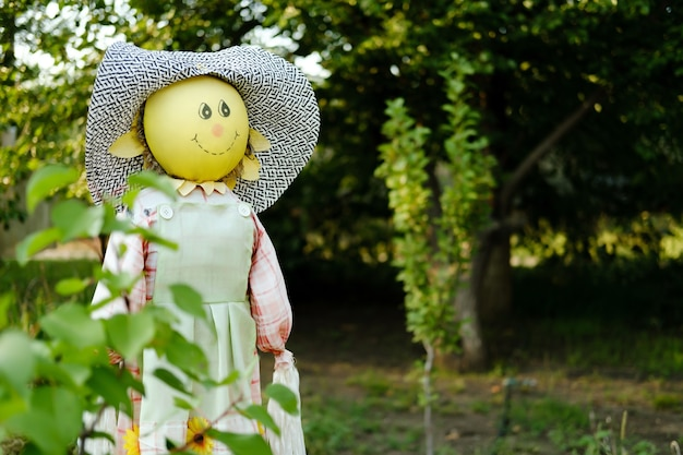A funny scarecrow in a garden full of green trees sunny summer day