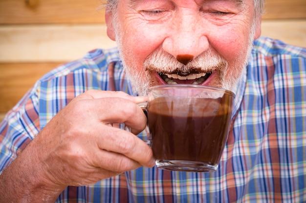 ホットチョコレートを飲んで顔を汚している素敵な年配の老人の肖像画の面白いシーン-成熟した人々は楽しいアルド笑いを楽しんでいます
