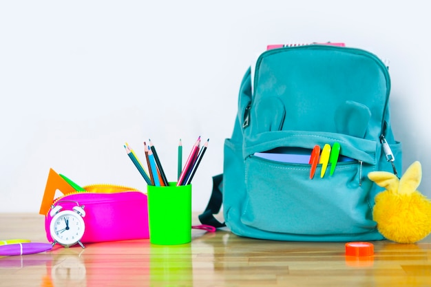 Funny school backpack with markers, bright pencil case, fluffy keychain glass with colored pencils and an alarm clock on a wooden table. back to school concept.