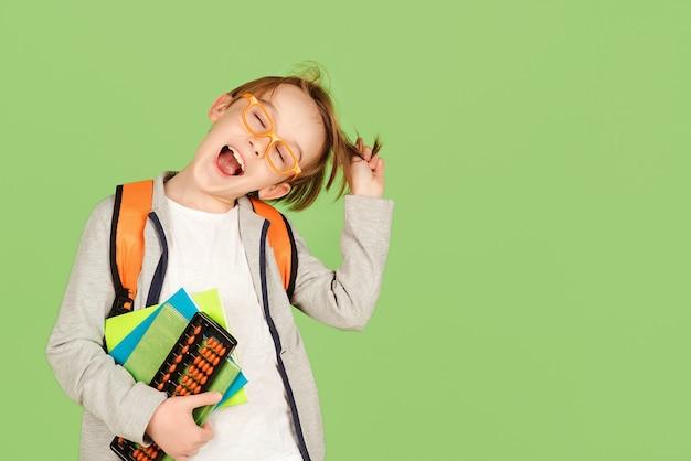 面白い男子生徒。バックパックとノートブックとメガネで幸せな子。学校と教育に戻る。クラスの学校の子供