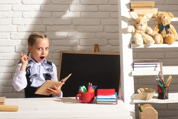 Funny school girl reading book in classroom at school portrait of lovely school girl in classroom at...