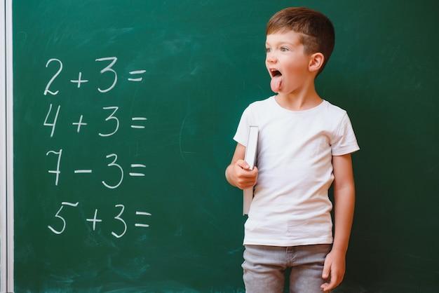 教室の緑の教育委員会の近くの面白い男子生徒。小学校。学校に戻る。