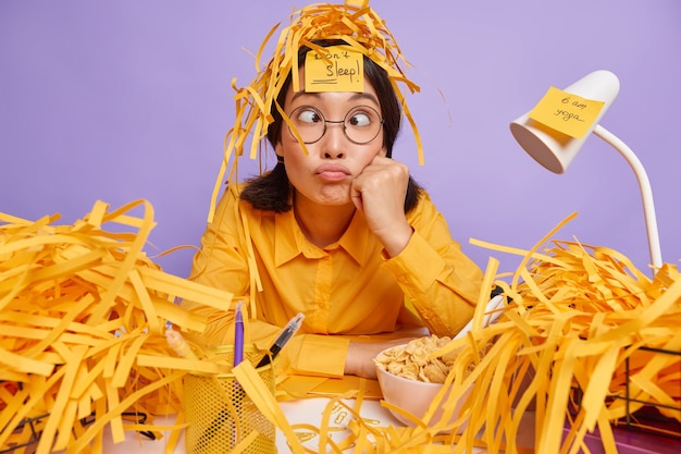 Funny schoolgirl prepares for test at home has sleepless night works late hours makes grimace has busy working schedule surrounded by paper wastes isolated over purple wall