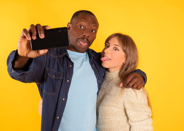 Funny selfie. cheerful interracial couple grimacing and showing tongues while taking a photo on smartphone, posing,