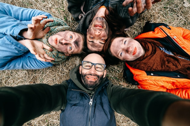 Funny selfie. group of friends with dirty stained faces fooling around. comic scary crazy spooky expressive faces. group of four people lying on grass. two men with pair of women enjoying party.