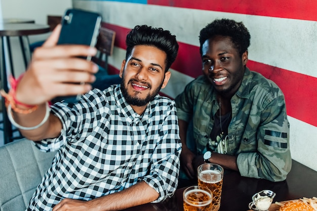Funny selfie. portrait of friends taking photo with smartphone while sitting at the table with beer and hamburgers.