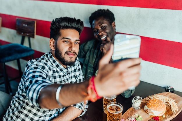 Смешное селфи. портрет друзей, делающих фото со смартфоном, сидя за столом с пивом и закусками.