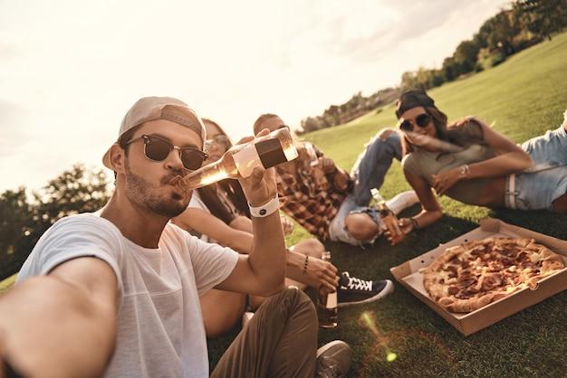 面白い自撮り!屋外でピザやビールを楽しみながら笑顔のカジュアルウェアの若者の自画像