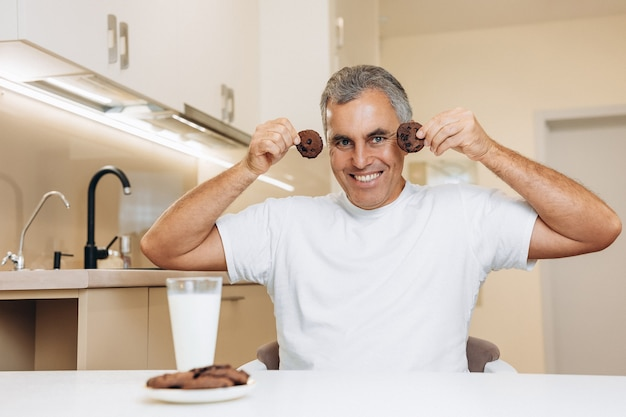 Funny senior man holding biscuits near the face and smiling with teeth en on background.