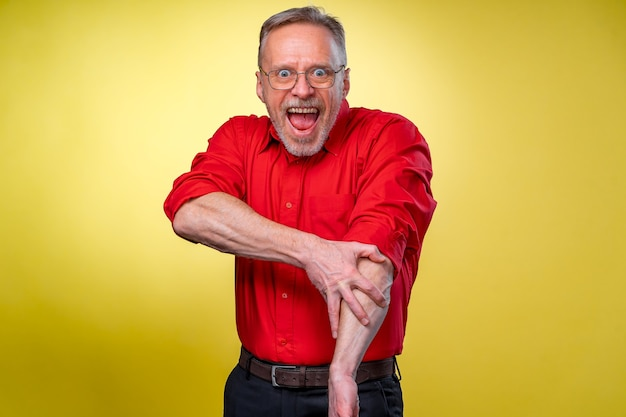 Funny senior man rolls shirt sleeves. ready for work. funny facial exprassions.