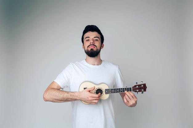 Забавный серьезный парень с укулеле в руках играет