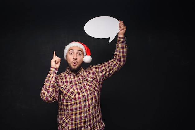 Funny serious  man in red christmas santa hat holds empty white cardboard as blank or mock up with copy space for text. black background