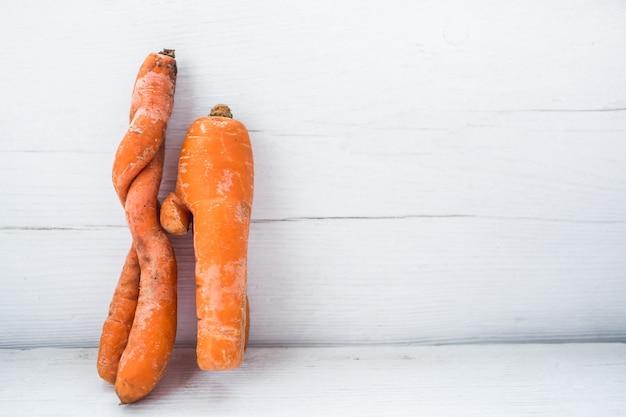 Смешная форма моркови на поверхности белой доски. две морковки занимаются сексом. скопируйте пространство.