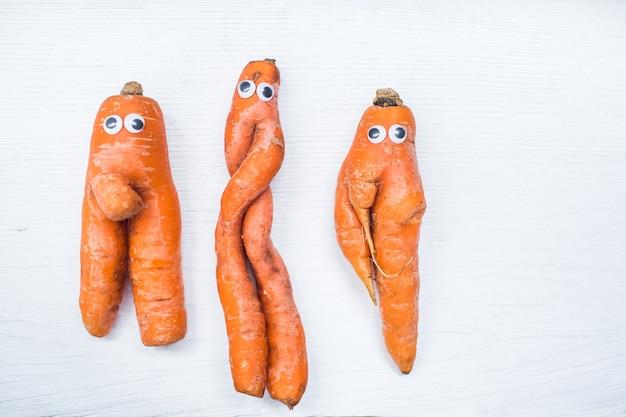Смешная форма моркови с глазами на поверхности белой доски. скопируйте пространство.