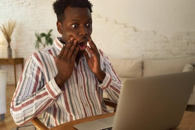 노트북과 함께 테이블에 앉아 뺨에 손을 잡고 절망적 인 표정을 갖는 캐주얼 옷에 재미 충격 젊은 어두운 피부 남자
