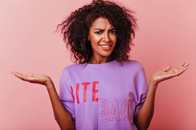 검은 눈을 가진 재미있는 짧은 머리 소녀. 분홍색에 서있는 감정적 인 세련 된 아프리카 여자.