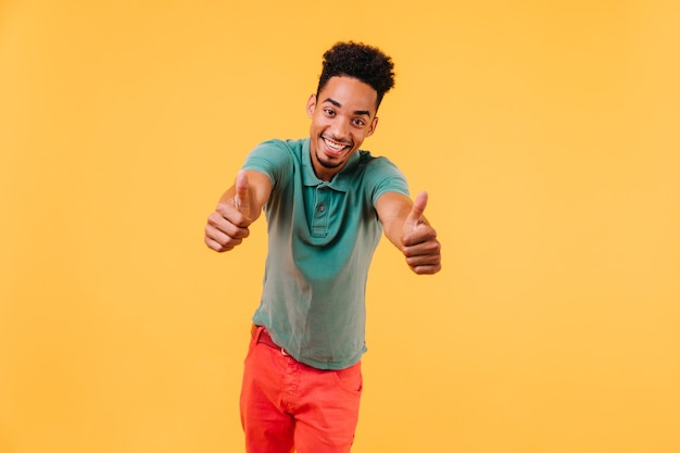 엄지 손가락으로 포즈를 취하는 재미있는 짧은 머리 남자. 유행 복장에 행복 한 아프리카 남자의 실내 사진.