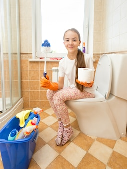 Funny shot of girl posing on toilet with brush and toilet paper like scepter and orb