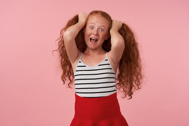 Funny shot of joyful redhead female kid with long curly hair fooling over pink background in red skirt and striped top, looking camera happily with wide mouth opened, making long ears from her hair