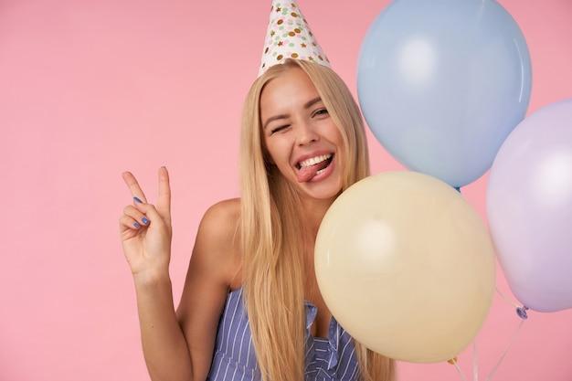 Colpo divertente di donna bionda dai capelli lunghi in abito estivo blu e cappello di compleanno in piedi su sfondo rosa, strizzando l'occhio alla telecamera con la lingua sporgente e alzando il gesto di vistory