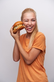Funny shot of lovely young blonde woman with ponytail hairstyle giving wink to camera and showing her tongue while posing over white background with fresh burger in her hands