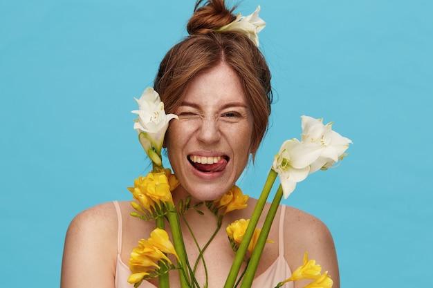 봄 꽃과 파란색 배경 위에 서, 속이는 동안 그녀의 혀를 유쾌하게 보여주는 롤빵 헤어 스타일을 가진 젊은 매력적인 빨간 머리 아가씨의 재미 있은 샷