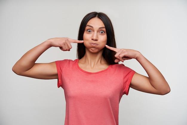 Забавный снимок молодой кареглазой брюнетки с естественным макияжем, держащей поднятыми указательными пальцами надутые щеки и дурачащейся стоя Бесплатные Фотографии