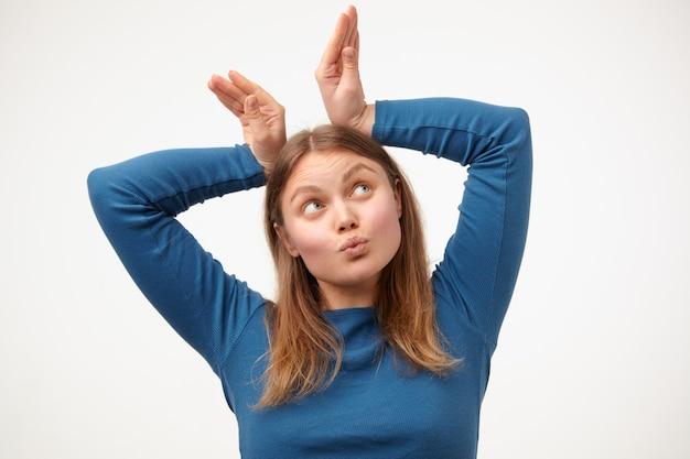 上げられた手のひらでパンの耳を模倣し、白い背景の上に立っている間顔を作るカジュアルな髪型の若い陽気なブロンドの女性の面白いショット