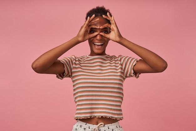 ピンクの壁に隔離された、眼鏡を模倣し、正面を元気に見ながら、顔に手を上げたままの若いうれしそうな茶色の髪の巻き毛の女性の面白いショット