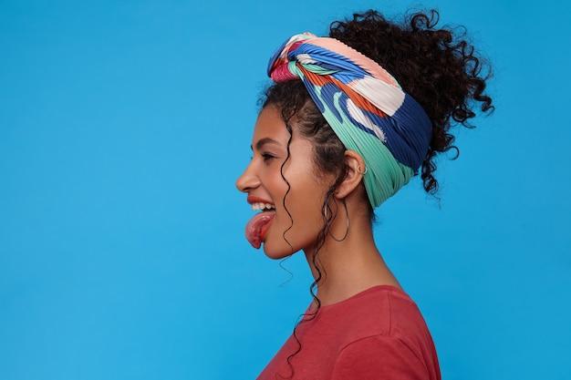 青い壁の上に立って、浮気しながら彼女の舌から元気に突き出ているお祝いの化粧をした若い楽しい黒髪の巻き毛の女性の面白いショット