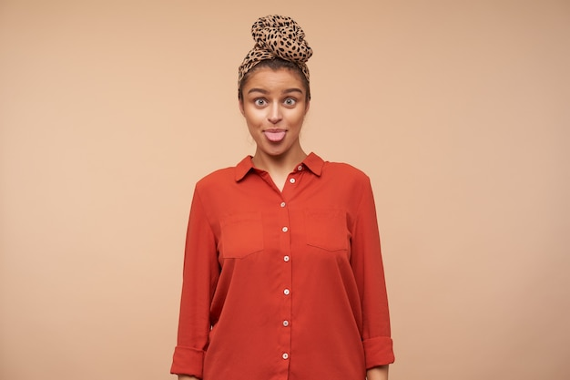 Funny shot of positive young lovely brown haired woman showing cheerfully her tongue while fooling, standing over beige wall in red shirt and headband
