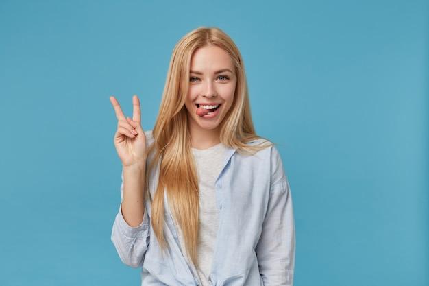Colpo divertente di giovane femmina bionda con acconciatura casual alzando la mano con segno di vittoria, guardando con un sorriso gioioso e mostrando la lingua, in piedi in camicia blu