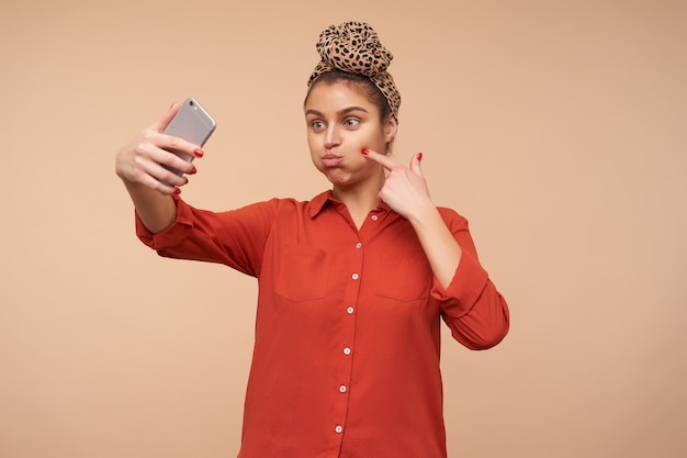 Funny shot of young cheerful brown haired lady puffing out her cheeks while fooling and making selfie with her smartphone, isolated over beige wall