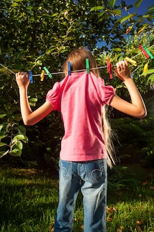 Funny shot of young girl hanging on clothesline at garden