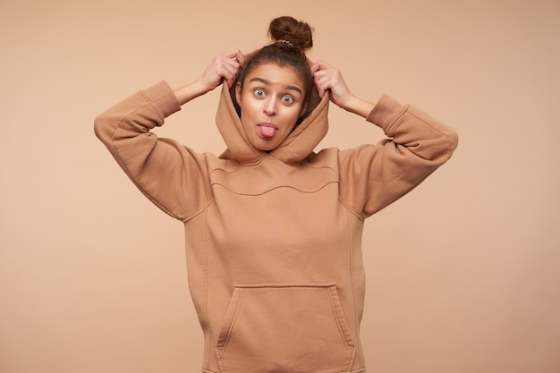 Funny shot of young lovely brown haired lady with bun hairstyle showing cheerfully tongue at front while taking on her hood, isolated over beige wall
