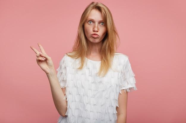 Colpo divertente di giovane donna adorabile con capelli volpi che solleva le dita con segno di pace e fa smorfie mentre si trova su sfondo rosa, vestita di t-shirt bianca festiva