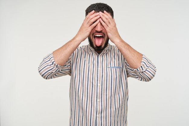 Colpo divertente di giovane uomo barbuto abbastanza mora con taglio di capelli corto che copre gli occhi con le mani alzate e sporge la lingua mentre si trova sul muro bianco